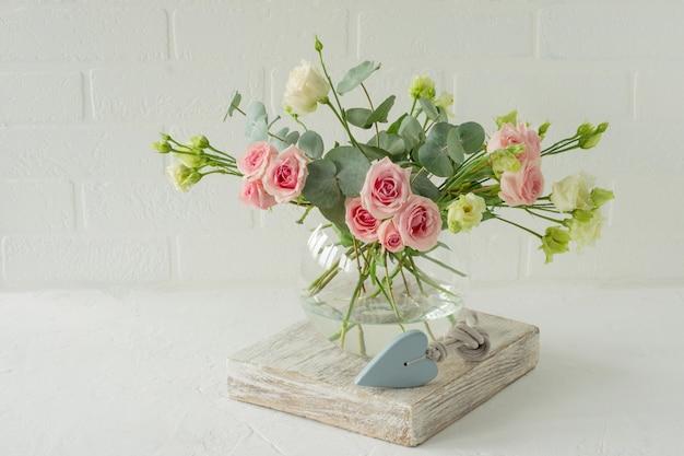 Blumenstrauß aus rosen, eustoma und eukalyptus in einer stilvollen glasvase auf einem tisch. blumenzusammensetzung