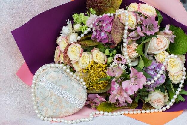 Blumenstrauß aus rosen, hortensien und einem herzen mit spitzen und perlen
