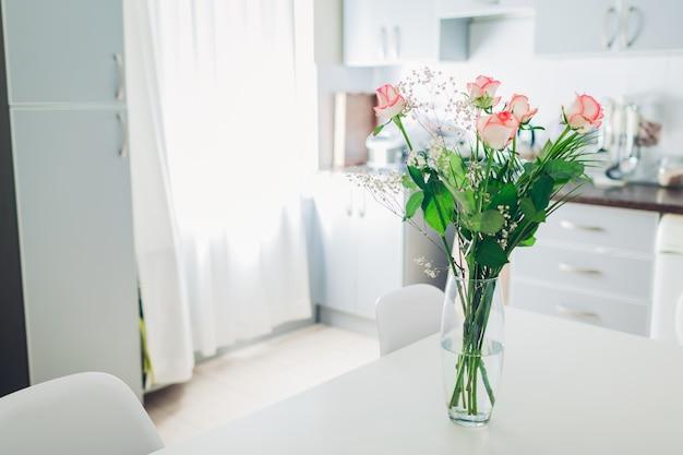 Blumenstrauß aus rosen in der küche. interieur mit blumen geschmückt.