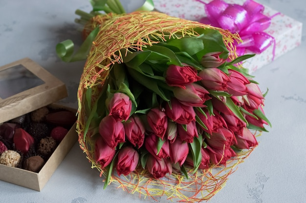 Blumenstrauß aus rosen, schachtel pralinen und geschenk zum valentinstag