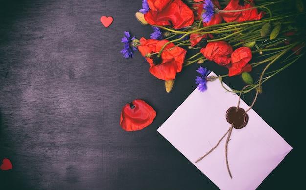 Blumenstrauß aus roten mohnblumen und einem weißen umschlag