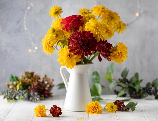 Blumenstrauß aus roten und gelben blumen im krug auf weißem tischherbstferienkonzept
