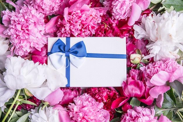 Blumenstrauß aus schönen rosa pfingstrosen mit geschenkbox grußkarte für den feiertag valentinstag