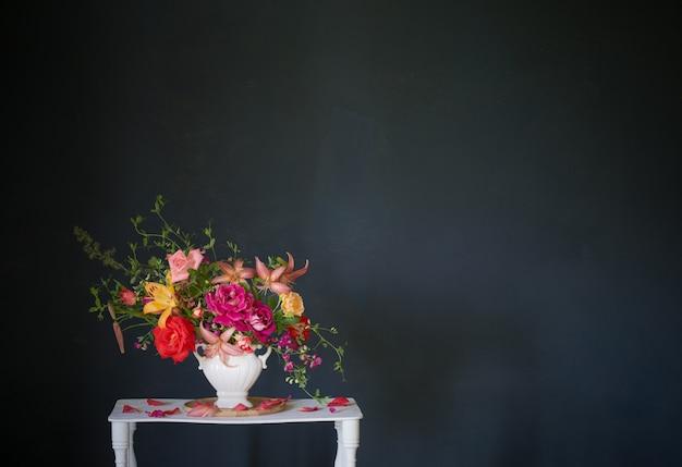 Blumenstrauß aus sommerblumen in vase auf weißem vintage-holzregal auf dunklem hintergrund