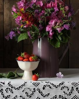 Blumenstrauß aus sommergartenblumen und erdbeeren auf dem tisch mit einer weißen spitzentischdecke rustikales interieur phlox löwenmaul ageratum in einem krug