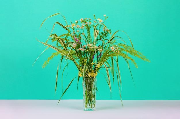 Blumenstrauß aus sommerkräutern, gänseblümchen und clematis in einer glasvase auf einer tadellosen farbe