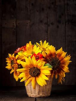 Blumenstrauß aus sonnenblumen im korb auf dem tisch über holzhintergrund