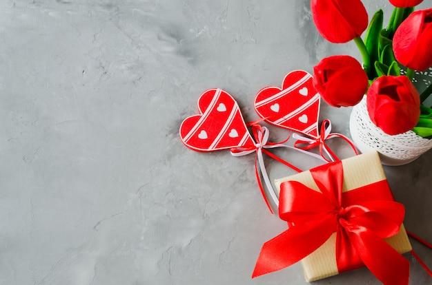 Blumenstrauß aus tulpen, geschenkbox und dekorativen herzen für valentinstag, damen- oder muttertag.