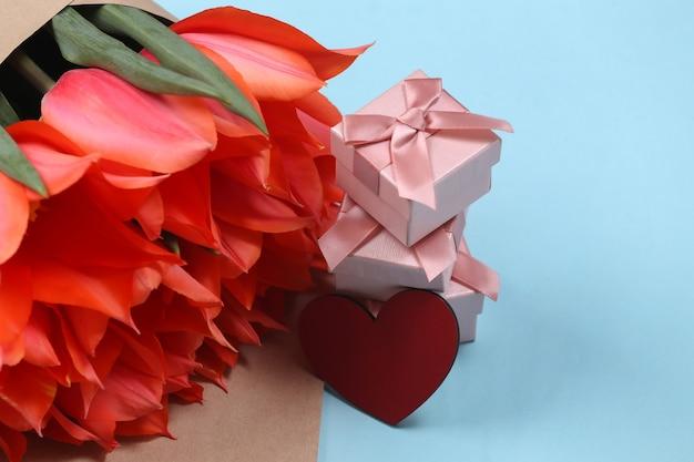 Blumenstrauß aus tulpen und geschenkboxen, herz auf blauem hintergrund. feiertag muttertag oder 8. märz, geburtstag.
