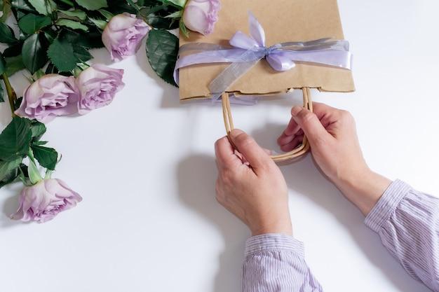 Blumenstrauß aus violetten rosen und frauenhänden mit einkaufstasche auf dem weißen hintergrund, ansicht von oben.
