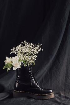 Blumenstrauß aus weißen blüten im dunklen lederstiefel