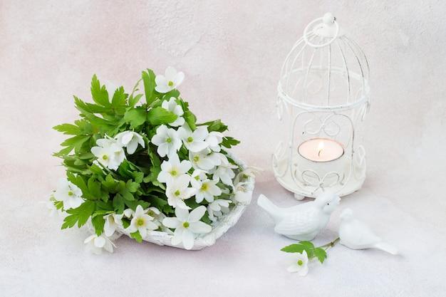 Blumenstrauß aus weißen blumen, vogelfiguren und einem käfigleuchter mit kerze