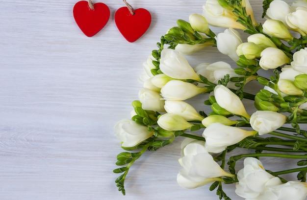 Blumenstrauß aus weißen freesien und zwei roten herzen aus holz