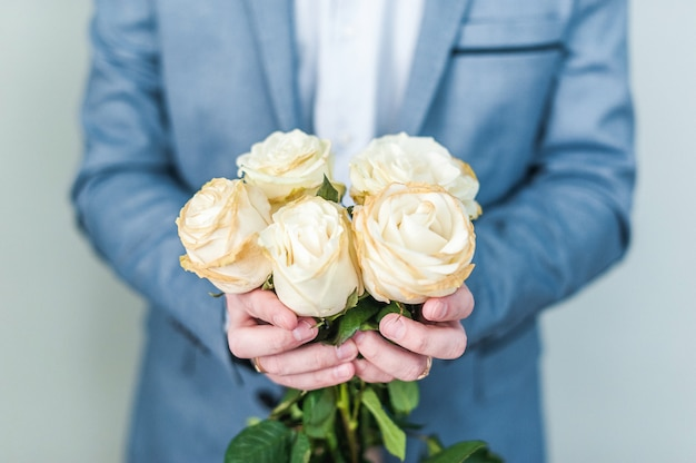 Blumenstrauß aus weißen rosen in den händen. valentinstag