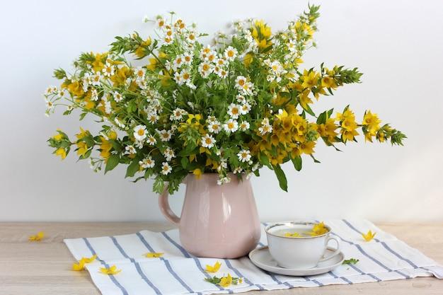 Blumenstrauß aus weißen und gelben blumen, lysimachia und kamille in einem krug und einer weißen tasse auf dem tisch.