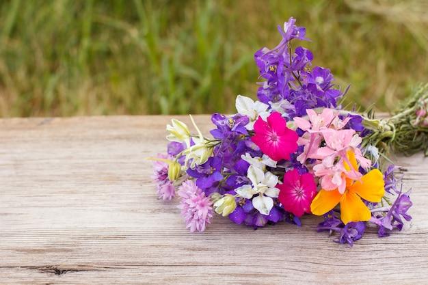 Blumenstrauß aus wildblumen auf altem holzbrett mit grünem naturhintergrund.