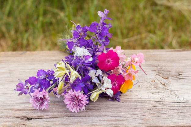 Blumenstrauß aus wildblumen auf altem holzbrett mit natürlichem hintergrund.