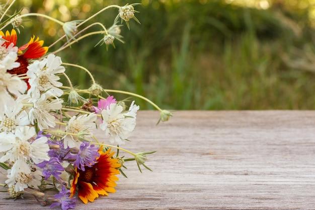 Blumenstrauß aus wildblumen auf altem holzbrett mit unscharfem natürlichen hintergrund.