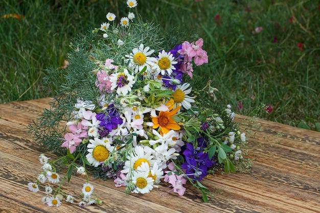 Blumenstrauß aus wildblumen auf alten holzbrettern mit der grünen naturoberfläche