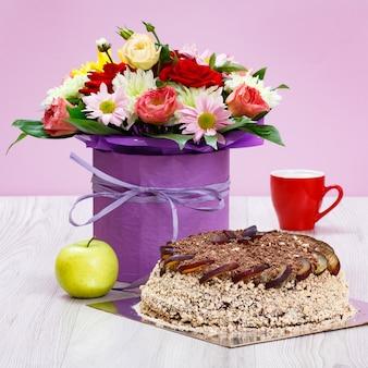 Blumenstrauß aus wildblumen, einem apfel, einem schokoladenkuchen und einer tasse kaffee auf den holzbrettern.