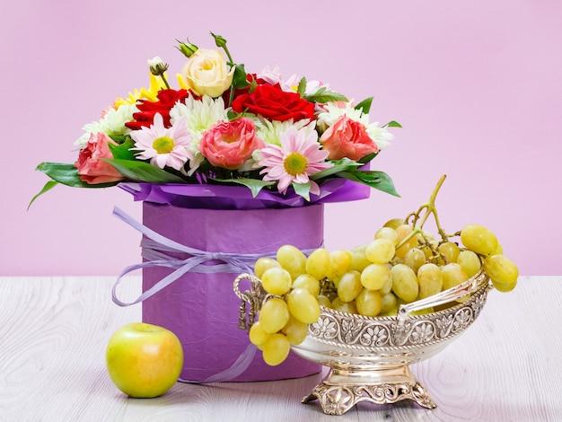 Blumenstrauß aus wildblumen, einem apfel und trauben in einer metallvase auf den holzbrettern