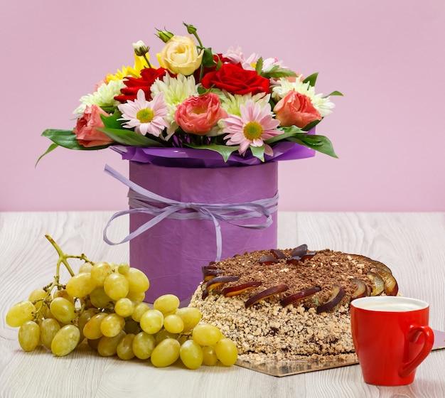 Blumenstrauß aus wildblumen, einem schokoladenkuchen, trauben und einer tasse kaffee auf den holzbrettern.