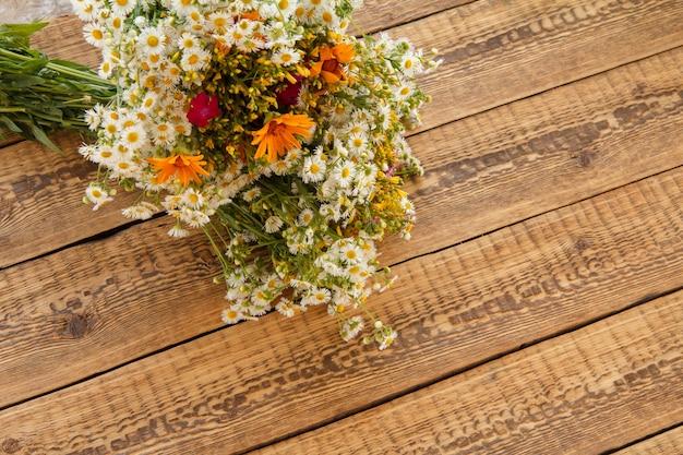Blumenstrauß aus wildblumen mit alten holzbrettern im hintergrund. ansicht von oben.