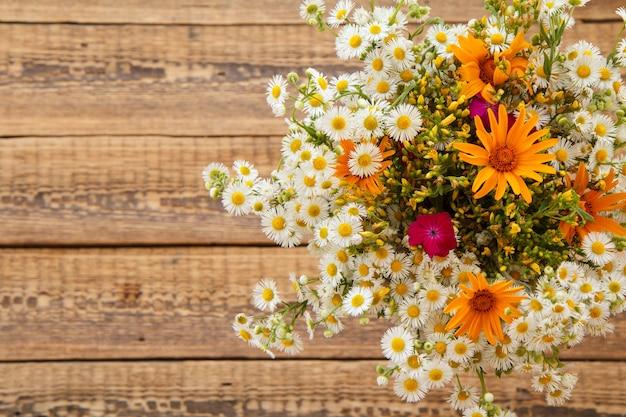 Blumenstrauß aus wildblumen mit alten holzbrettern im hintergrund.