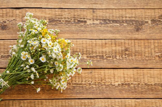 Blumenstrauß aus wildblumen mit kamille auf alten holzbrettern. draufsicht mit kopienraum.