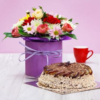 Blumenstrauß aus wildblumen, schokoladenkuchen und eine tasse kaffee auf den holzbrettern