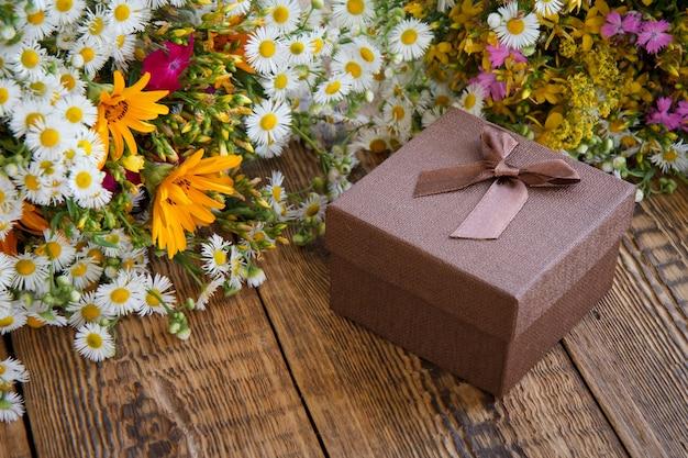 Blumenstrauß aus wildblumen und brauner geschenkbox auf alten holzbrettern. ansicht von oben.