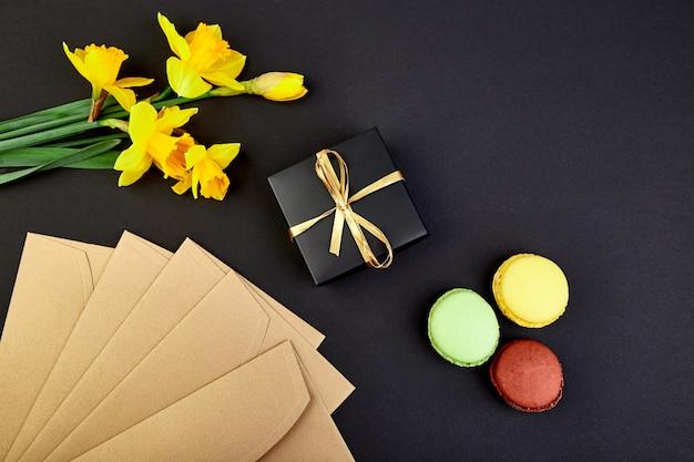 Blumenstrauß blüht narzissengeschenk und bonbons oder kuchen macarons.