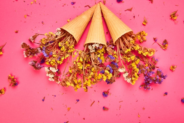 Blumenstrauß blumen in einem waffelkegel auf einer rosa oberfläche
