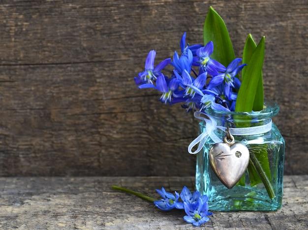 Blumenstrauß der blauen scilla-frühlingsblumen in einer glasvase auf altem hölzernem hintergrund. selektiver fokus.