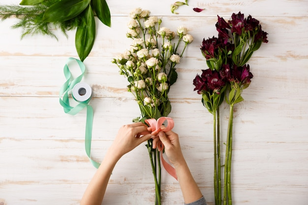 Blumenstrauß der draufsicht von blumen auf holztisch