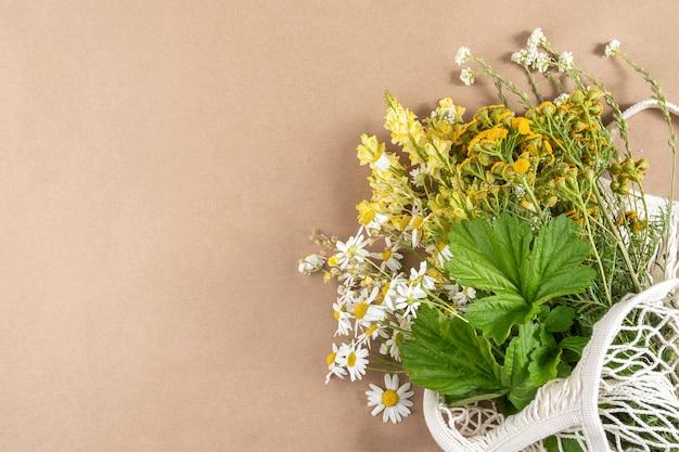 Blumenstrauß der feldblumen in der öko-tasche auf beigem hintergrund. konzept kein plastik und kein abfall.