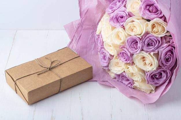Blumenstrauß der frischen erstaunlichen weißen und lila rosen und bastelgeschenkbox auf weißem hintergrund. geschenk für urlaub mutter, valentinstag, geburtstag, jubiläum und hochzeitstext.