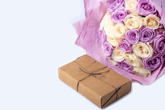 Blumenstrauß der frischen erstaunlichen weißen und lila rosen und bastelgeschenkbox auf weißem hintergrund.