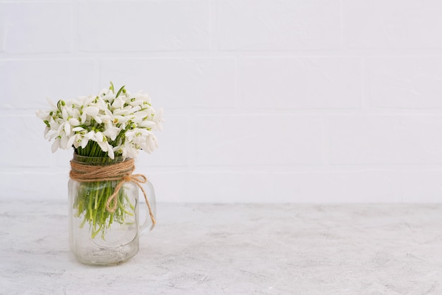 Blumenstrauß der frühlingsblumen der schneeglöckchen in einer glasvase auf einer hellen backsteinmauer.