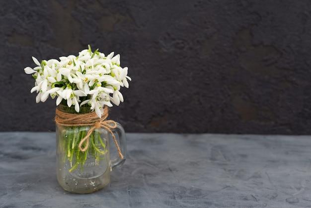 Blumenstrauß der frühlingsblumen der schneeglöckchen in einer glasvase.