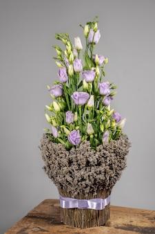 Blumenstrauß der frühlingsblumen im land rustikalen stil auf grauem hintergrund