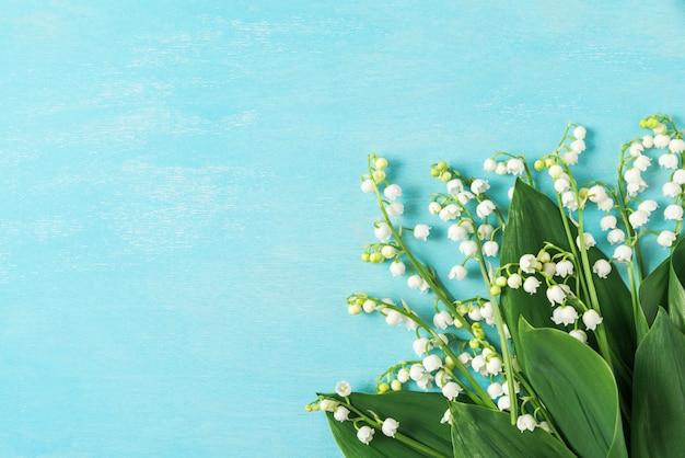 Blumenstrauß der frühlingsblumen maiglöckchen auf blauem holzhintergrund. draufsicht mit kopierraum. flach liegen