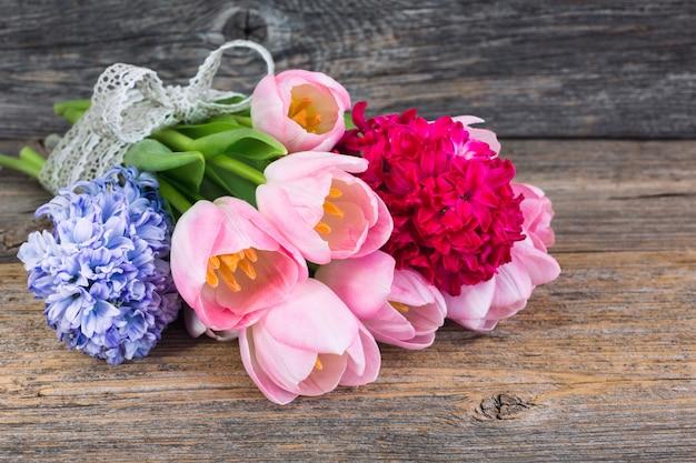 Blumenstrauß der frühlingsblumen verziert mit band auf altem holztisch. weicher fokus