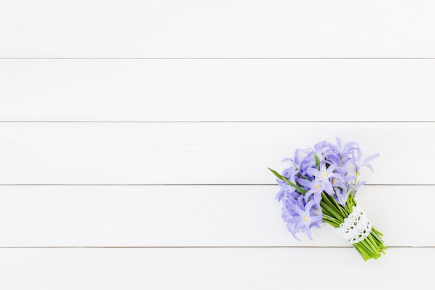 Blumenstrauß der frühlingsblumen verziert mit spitze auf weißer holzwand. draufsicht, kopierraum