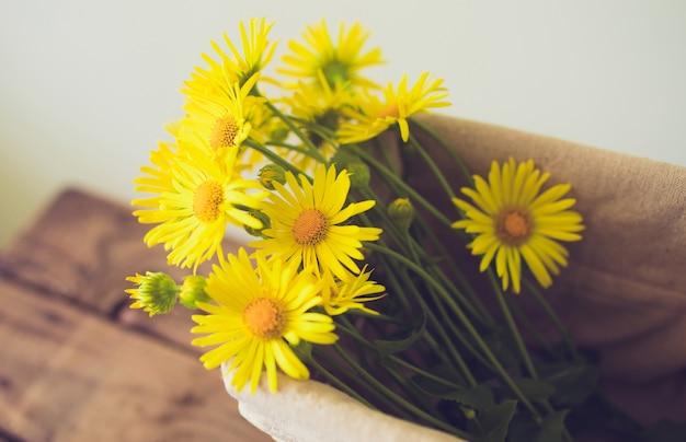 Blumenstrauß der gelben blumen in einem korb auf holz