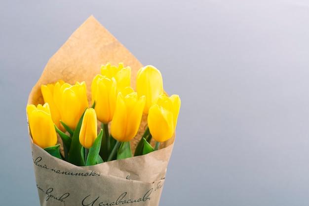 Blumenstrauß der gelben tulpen auf einem grauen hintergrund mit platz für text