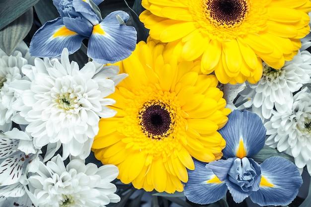 Blumenstrauß der gelben und blauen blumen im weinlesestil.