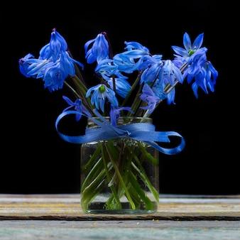 Blumenstrauß der glockenblumenblume in einem vase auf dem tisch auf einer schwarzen hintergrundnahaufnahme