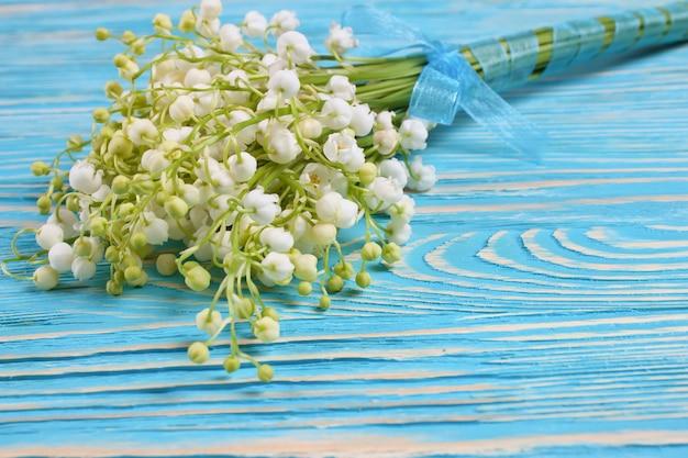 Blumenstrauß der maiglöckchen auf dem blauen hölzernen hintergrund mit raum für text