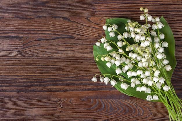 Blumenstrauß der maiglöckchen auf dem braunen hölzernen hintergrund. draufsicht, flach liegen mit platz für text